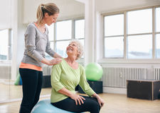 Older woman assisted by personal trainer at gym Stock Images