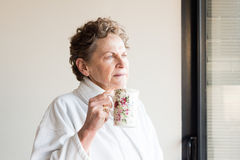 Older woman in bathrobe with cup of tea Royalty Free Stock Image