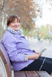 Older woman  on bench in autumn park. Stock Image