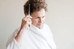 Older woman brushing hair royalty free stock image