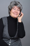 Older woman calling. Attractive older woman talking on the phone and laughing Stock Images