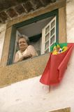 An older woman celebrates soccer victory by hanging Portuguese flag out the window of Tomar, Portugal Royalty Free Stock Photography