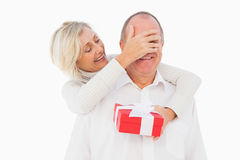 Older woman covering her partners eye while holding present Royalty Free Stock Photography