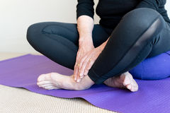 Older woman cross legged. Close up of older woman's hands and feet, sitting cross legged on purple yoga mat and cushion (selective focus Royalty Free Stock Photos