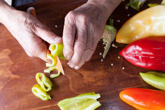 Older woman cutting pepper Royalty Free Stock Images