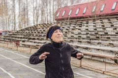 Older woman doing outdoor exercise. Healthy lifestyle in old age. older woman doing outdoor exercise. pensioner doing exercise for hands stock photo