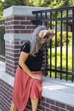 Older woman with dress and sunglasses and long gray hair sits by fence outside estate or park leaning on her arm in distress or sa stock photography
