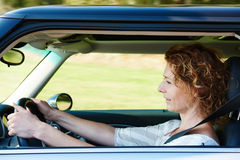 Older woman driving car. Side portrait of an older woman driving car Royalty Free Stock Image