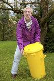 Older woman with dustbin in garden Royalty Free Stock Images