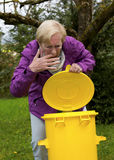 Older woman with dustbin in garden Royalty Free Stock Photography
