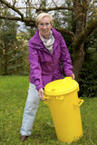 Older woman with dustbin in garden Stock Image