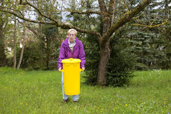 Older woman with dustbin Stock Photos