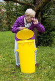Older woman with dustbin in garden Royalty Free Stock Photos