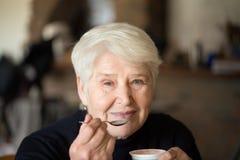 Older woman eats yogurt. Older woman with grey hair eats yogurt with spoon Royalty Free Stock Photos