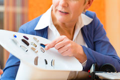 Deaf woman with hearing aid. Older woman or female pensioner with a hearing problem make a hearing test and may need a hearing aid, she looking on a selection of Royalty Free Stock Photography