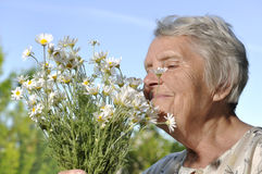 Older woman with flowers. Royalty Free Stock Photo