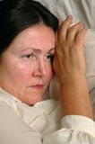 Older woman, grieving alone. Sad older woman lying on bed, unhappy royalty free stock photography
