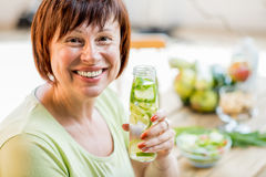 Older woman with healthy food indoors. Older woman in green t-shirt drinking fresh detox drink from the bottle indoors Stock Photo