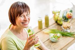 Older woman with healthy food indoors. Older woman in green t-shirt drinking fresh detox drink from the bottle indoors Royalty Free Stock Image