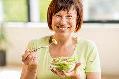 Older woman with healthy food indoors. Portrait of a beautiful older woman in green t-shirt holding a salad indoors Royalty Free Stock Photo