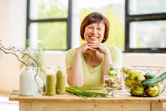Older woman with healthy food indoors. Portrait of a beautiful older woman with green healthy food on the table indoors on the window background Royalty Free Stock Photo