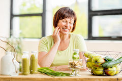 Older woman with healthy food indoors. Portrait of a beautiful older woman with green healthy food on the table indoors on the window background Stock Photo