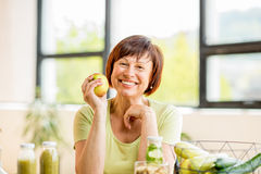 Older woman with healthy food indoors. Portrait of a beautiful older woman with green healthy food on the table indoors on the window background Stock Image