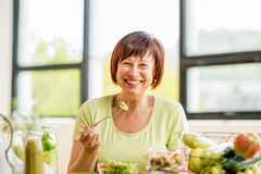 Older woman with healthy food indoors. Portrait of a beautiful older woman with green healthy food on the table indoors on the window background Stock Photography