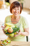 Older woman with healthy food indoors. Smiling older woman holding fruits and vegetables indoors Royalty Free Stock Images
