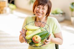 Older woman with healthy food indoors. Smiling older woman holding fruits and vegetables indoors Stock Images