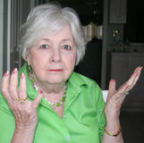 Older woman holding up both her hands. In exasperation stock photos