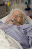 Older woman in hospital bed with oxygen mask Royalty Free Stock Photos