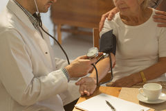 Older woman and hypertension. Older sick women with hypertension having her blood pressure checking by doctor Stock Photo