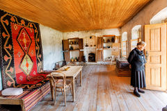 Older woman inside the house-museum of famous Georgian painter Niko Pirosmani in village where he lived last years Royalty Free Stock Photography