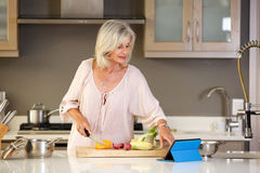 Older woman in kitchen reading recipe on tablet Stock Images