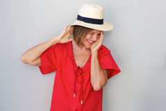 Older woman laughing with hat against gray wall. Portrait of older woman laughing with hat against gray wall Royalty Free Stock Photography