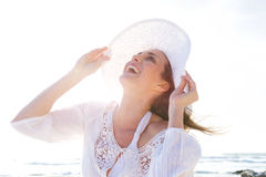 Older woman laughing with hat at the beach stock photography