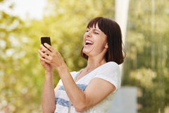 Older woman laughing looking at smart phone Royalty Free Stock Photos