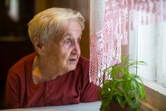 Older woman with longing looks out the window. Sad. Older woman with longing looks out the window royalty free stock photo