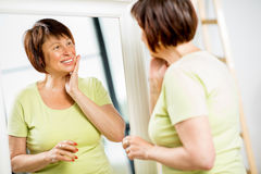 Older woman looking into the mirror royalty free stock images