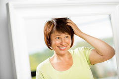 Older woman looking into the mirror stock images