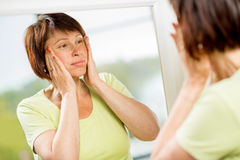 Older woman looking into the mirror. Sad older woman looking at her face into the mirror worried about the wrinkles Royalty Free Stock Photos