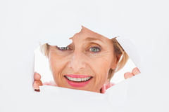 Older woman looking through rip Royalty Free Stock Images