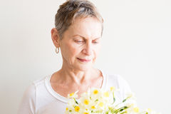 Older woman looking at spring flowers Stock Photography