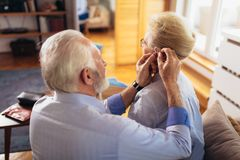 Woman and man or pensioners with a hearing problem. Older women and men or pensioners with a hearing problem stock images
