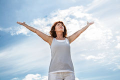 Older woman opening up her arms to exercise yoga outdoors. Breathing outside - older yoga woman opening up her arms to exercise,practicing meditation for freedom Royalty Free Stock Photo