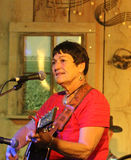 Older woman plays guitar and sings Stock Photography