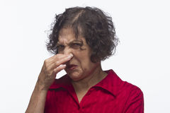 Older woman plugs her nose, horizontal Stock Photography