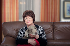 Older woman posing with dog on leather couch Stock Photo