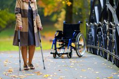 Older woman practicing walking on crutches Stock Photos